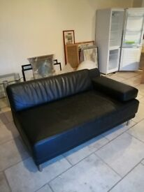 Two seater black leather sofa in good condition