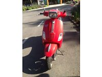 Red Vespa with helmets