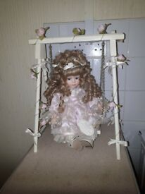 Leonardo collectible porcelain doll on a swing