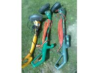 three electric grass strimmers