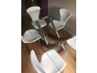 Glass dining table with 6 stylish cream coloured chairs