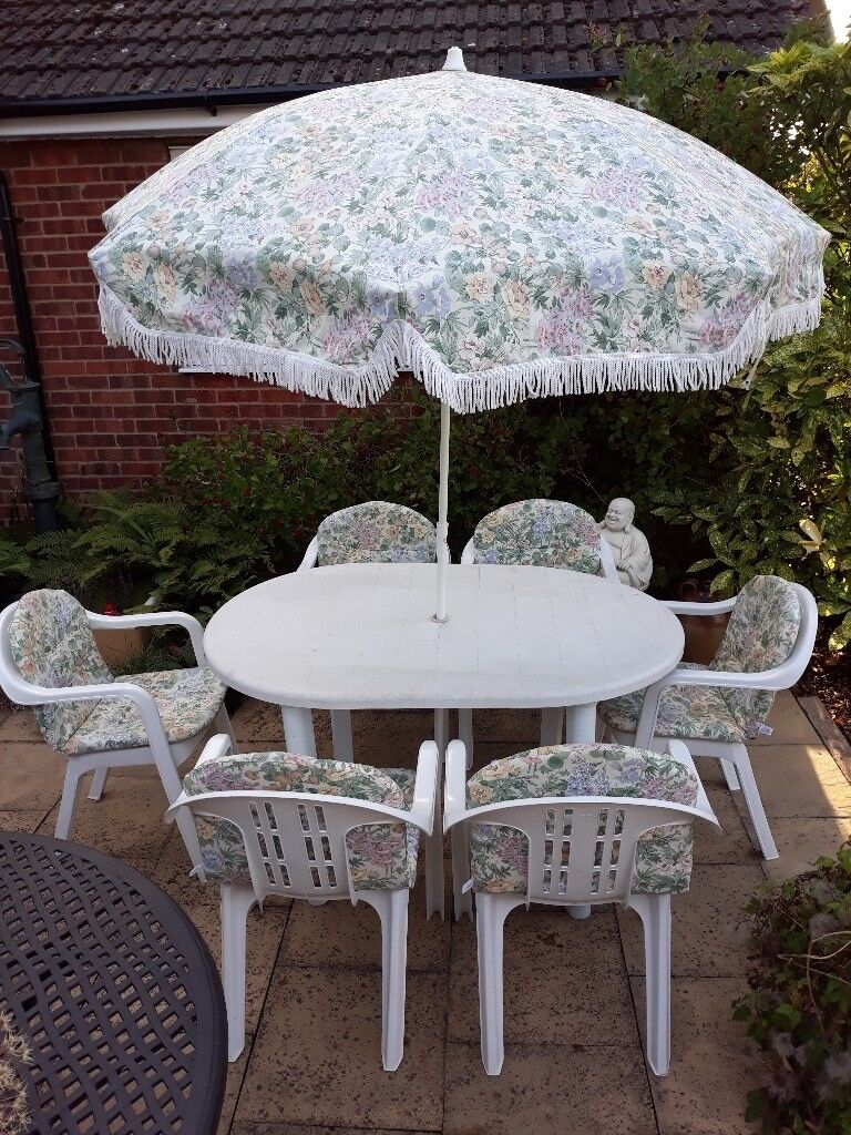 White nova outdoor table with six chairs cushions and matching parasol grimsby