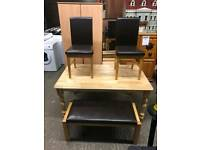 Oak table with 2 black leather chairs and a leather seating bench