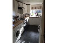 White kitchen units and wooden work tops