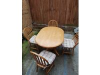 Dining table and four chairs with cushions.