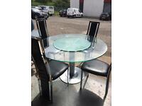 Glass table with spinning middle section, including 4 black Leather / metal chairs