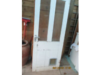 Old 4 panel wooden door 1895 x 755 x 35mm, probably pine, with upper glass panels and cat flap
