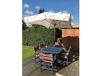 Large wooden garden table, 6 chairs & parasol with covers