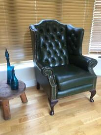 Vintage heavy bottle green leather wing back chair with copper nails.