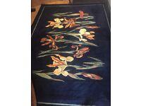 Striking black/coloured rug for sale