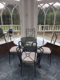 Metal & glass dining table with 4 chairs. Table is 1060mm diameter and is 750mm high.