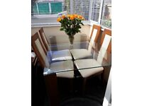 Lovely dinning room glass top table four matching chairs.A very good bargain