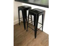 2 black industrial style stools