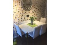 White high gloss dining table and 4 leather effect chairs