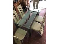 Glass dining table with six cream leather chairs