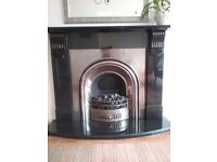 Black marble fire surround and hearth with silver coloured electric fire