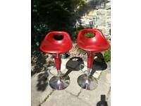 A pair of red kitchen / bar stools