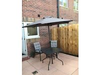 Tempered glass patio table, 2 chairs with cushions and parasol.
