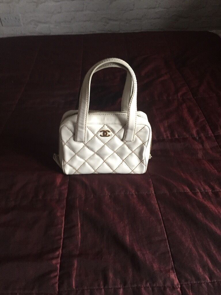 Chanel handbag white with gold stitching.