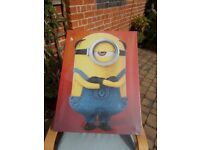 A MINIONS PICTURE ON CANVAS, NEW STILL HAS PLASTIC COVERING, SIZE H- 32 inches, W- 23.5 inches.