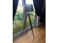 Beautiful grey lamp on wooden tripod