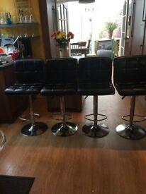 Four black bar stools