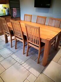 Solid Oak kitchen table with 6 leather top chairs for sale.