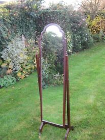 A tall tilting mirror in a mahogany frame.