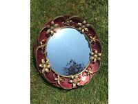 Vintage circular, bullseye, convex mirror.Gold coloured metal flowers/scrolls, dark red metal frame.