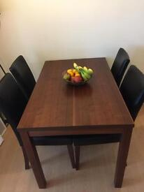 Dark wood dining table with 4 black leather chairs