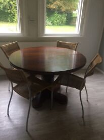 Round extending dining table with central pedestal