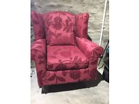 A pair of nearly new wing backed rich red arm chairs