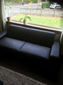 Black 3 seater sofa bed in leather look.