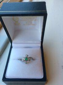 Platinum emerald & diamond crossover ring