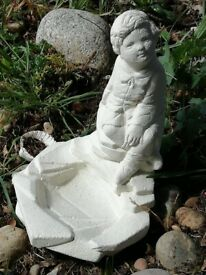 Lovely stone garden statue of a sitting boy by a pond