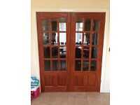 Solid hardwood pine doors in excellent condition with clear bevelled glass.