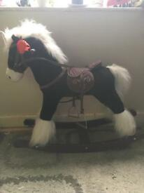 Kids black and white rocking horse, with brown saddle and stirrups