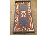 Brand new blue wool rug with design still in packaging