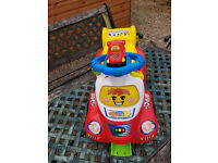 Vtech baby sit on car with small racing car.