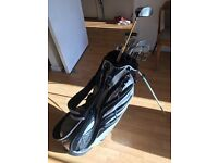 Full set of high quality graphite shaft golf clubs and putter. Includes silver Nike golf bag.