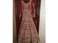 Beautiful red and gold full on stone work lengha/dress with a long trai