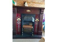 Dark wood and tiled fireplace with fire