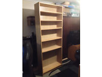 High, solid bookshelf in good condition.
