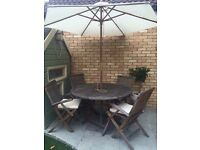 Solid teak garden table and chairs plus seat pads with parasol,