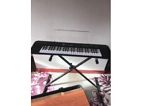 Casio electric keyboard with stand, carry bag and books