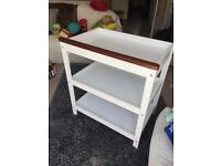 White wooden baby changing unit with shelves