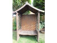 Wooden Gazebo with Latticed sides and slatted seat.