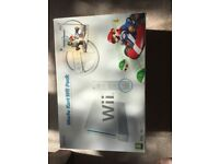 Wii console with wheels and hand remotes + Mario Kart.