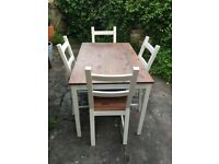 Solid wooden table with four chairs. Table top measures 1.2m x 0.75m.
