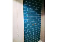Teal metro tiles and large gray tiles with white grout